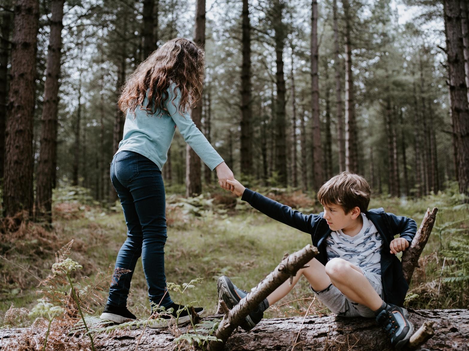 Brunette girl helping brunette boy stand up in forest