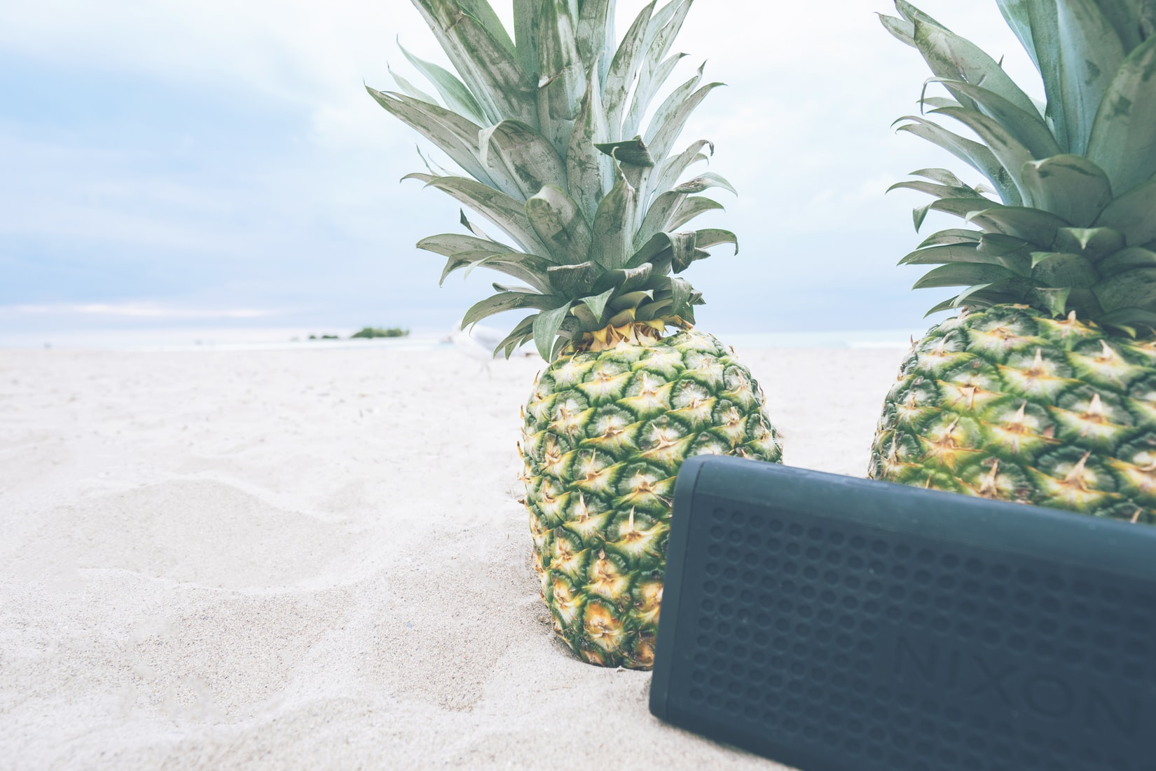 Black portable Nixon speaker next to two pineapples on sand