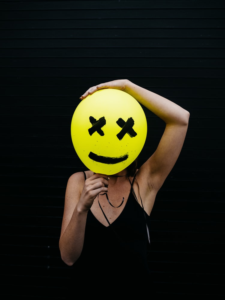 Woman holding yellow smiley balloon with X eyes