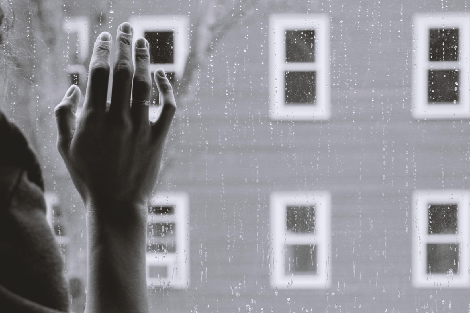 Grayscale photography of woman's right hand on window