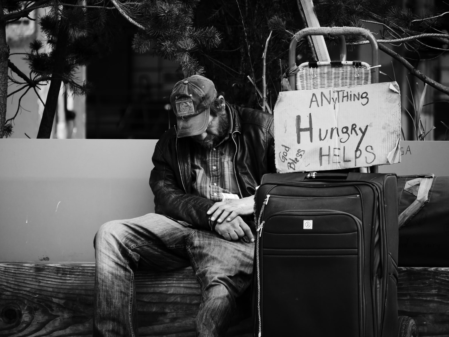Grayscale photography of homeless man sitting on bench next to luggage and cardboard sign
