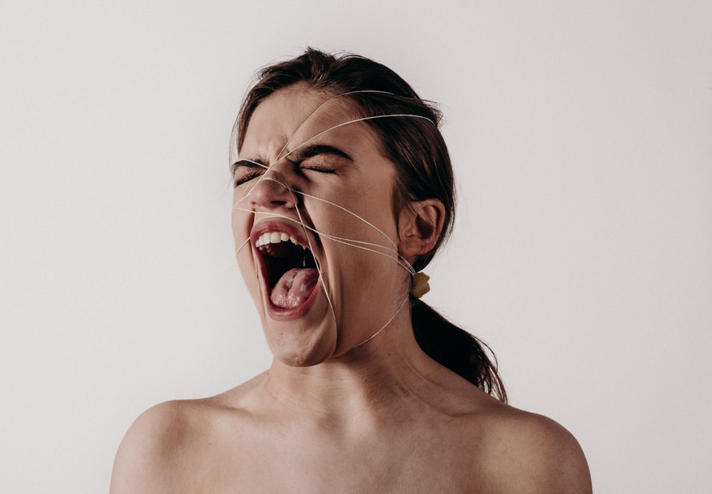Middle-aged brunette woman yelling with strings attached to face