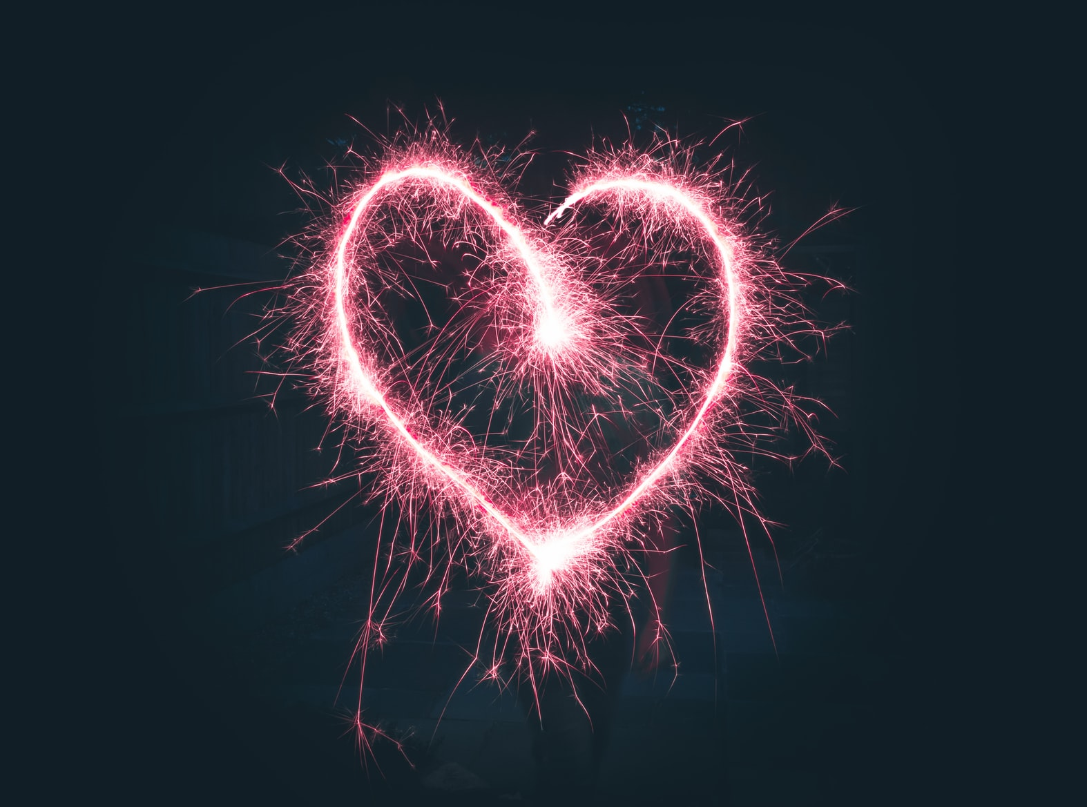 Pink heart-shaped sparklers on dark background