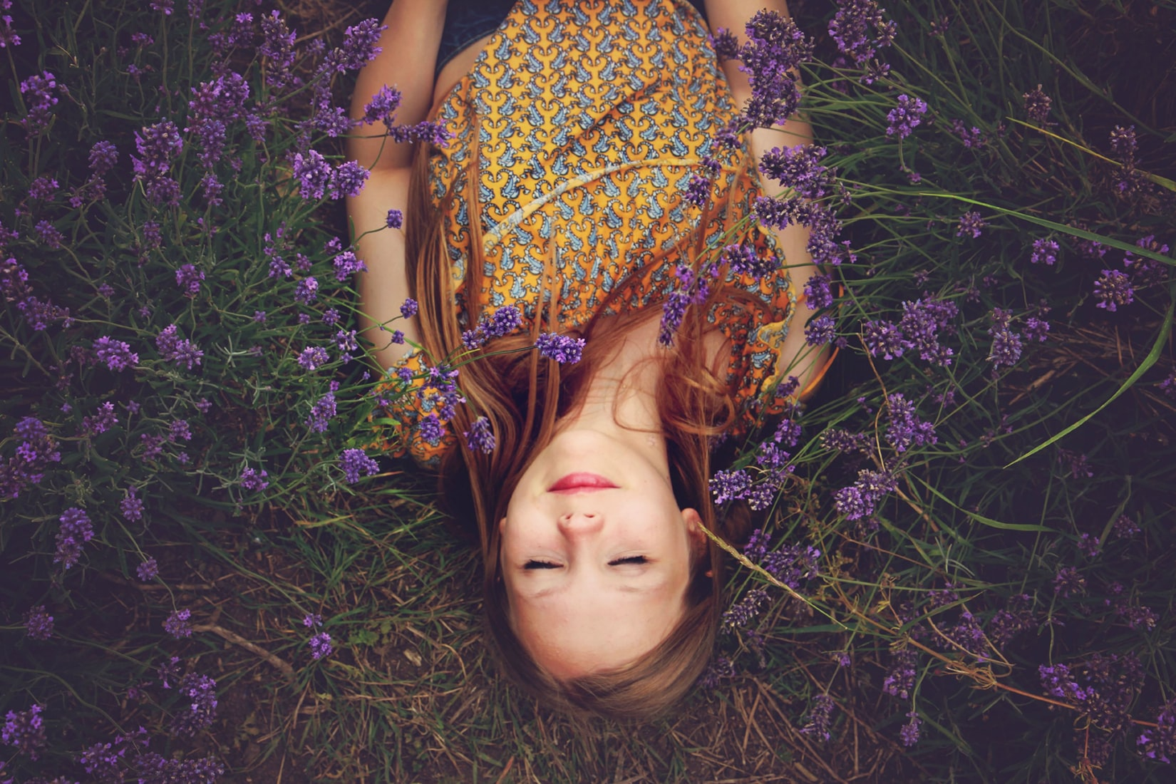 Woman in yellow top sleeping in nature next to lavenders