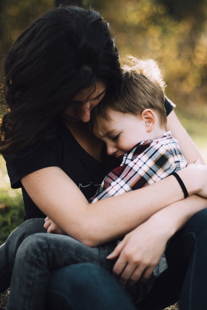 Mother hugging autistic boy on her lap