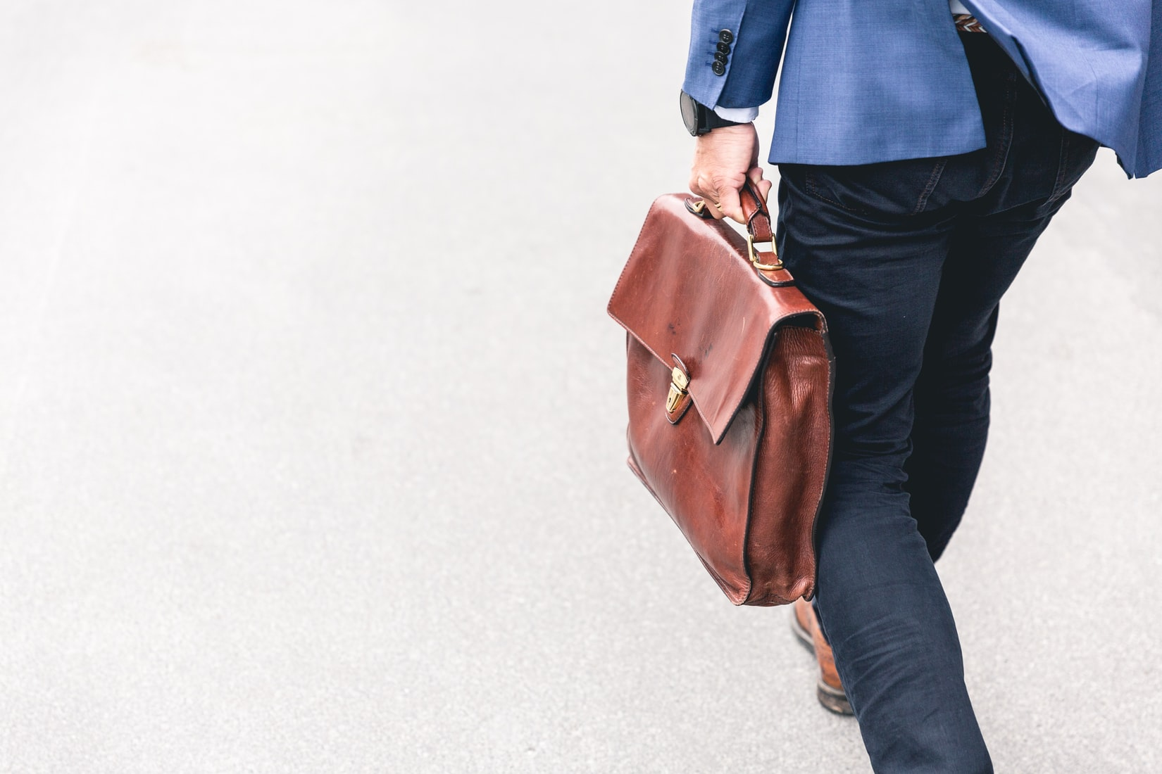 Person walking back to work and holding brown leather bag