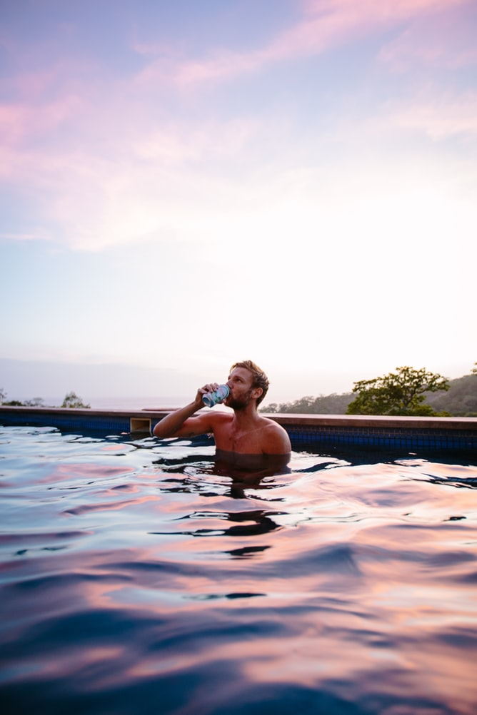 Topless man drinking beer in swimming pool