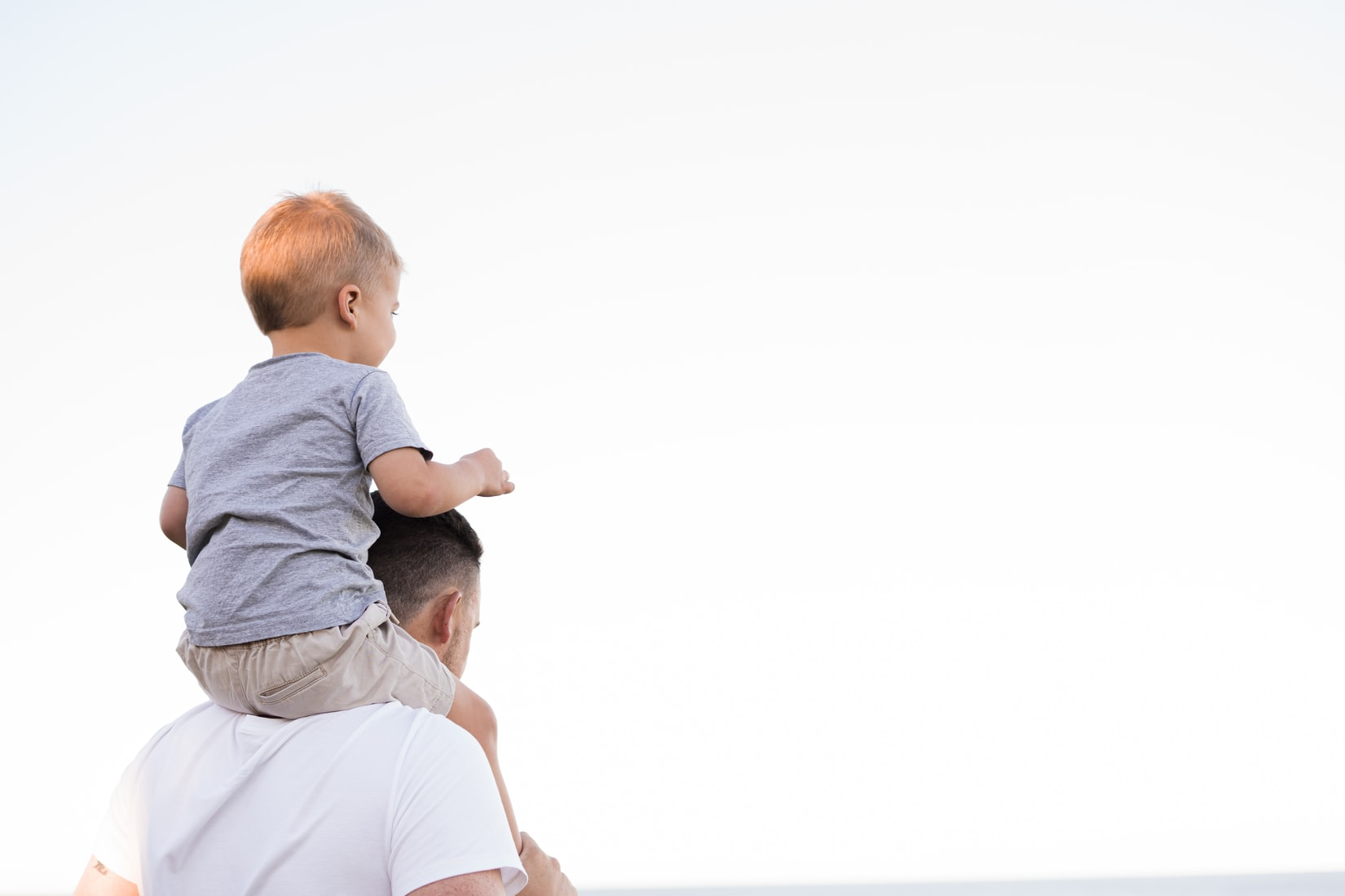Father in white shirt carrying blonde boy on shoulders