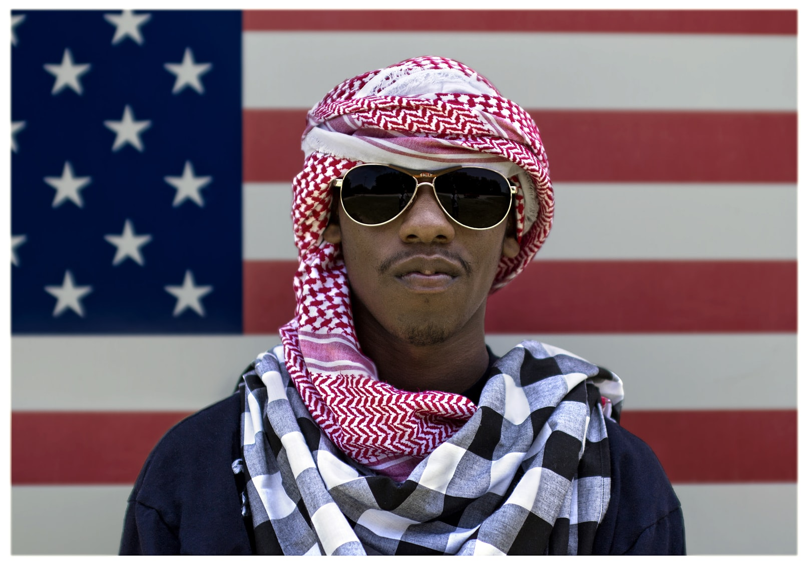 Black man wearing a keffiyeh and sunglasses in front of American flag