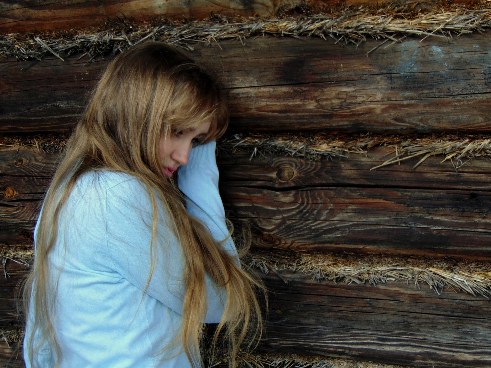 Depressed blonde woman leaning against brown wooden wall