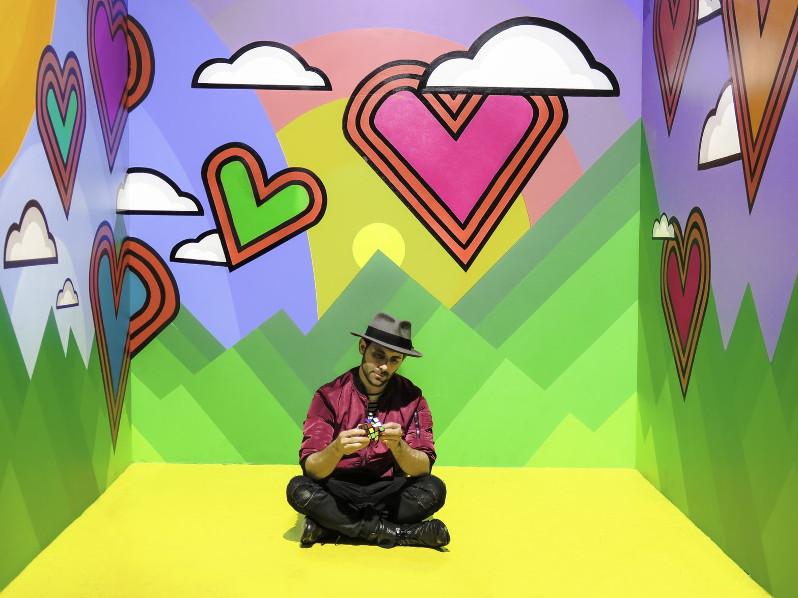 Man playing with Rubik's cube and sitting on floor in multicolored 3D wallpaper room