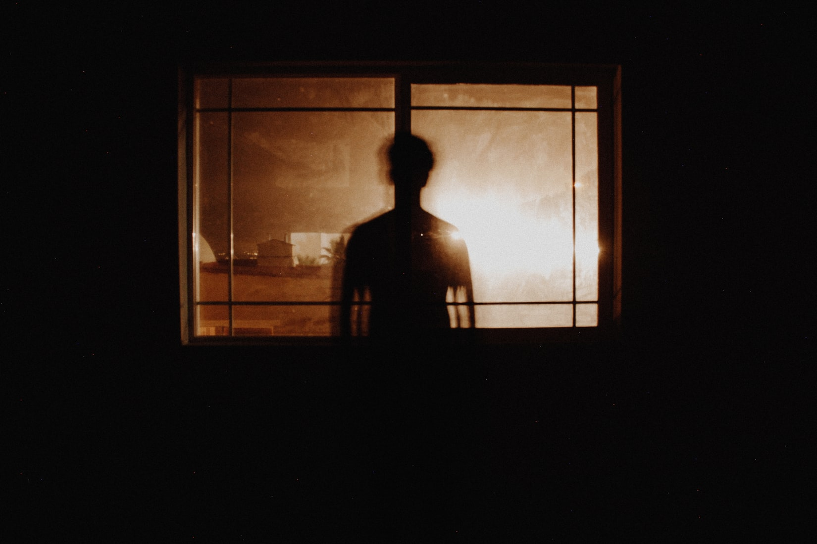 Silhouette photography of man in front of window in dark room