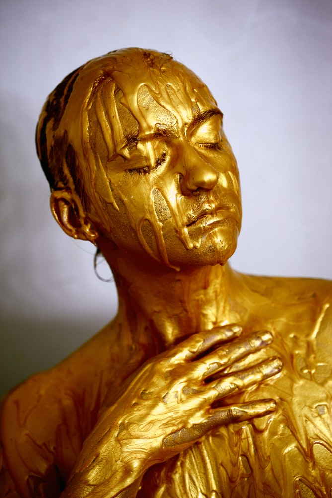 Person with eyes closed posing in golden colored liquid coating