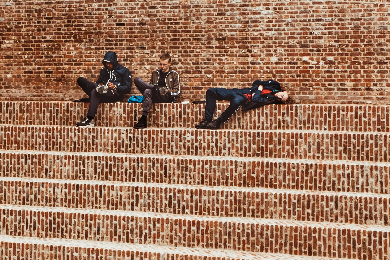 Three men sitting on brick stairs outdoors
