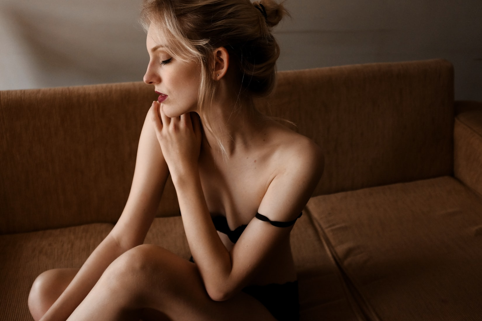 Blonde woman with low libido wearing black underwear and sitting on brown couch