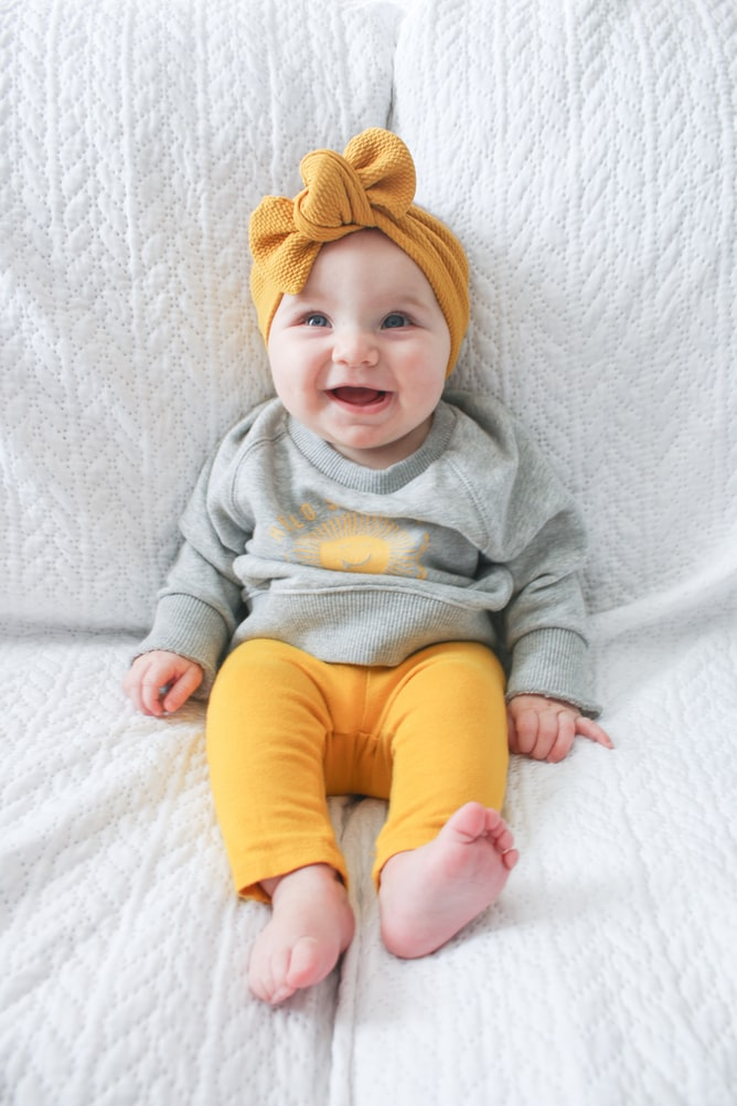 Baby dressed in yellow pants and smiling sitting on white sofa
