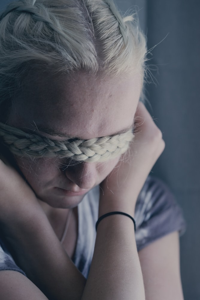 Sad blonde girl covering her eyes with braided hair
