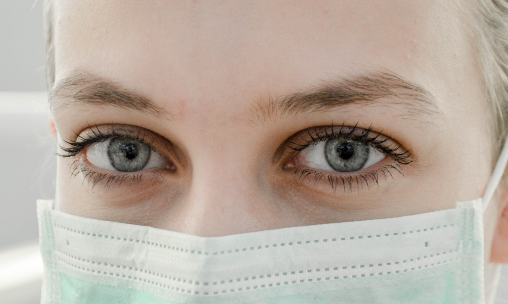 Closeup photo of woman with blue eyes wearing surgical mask