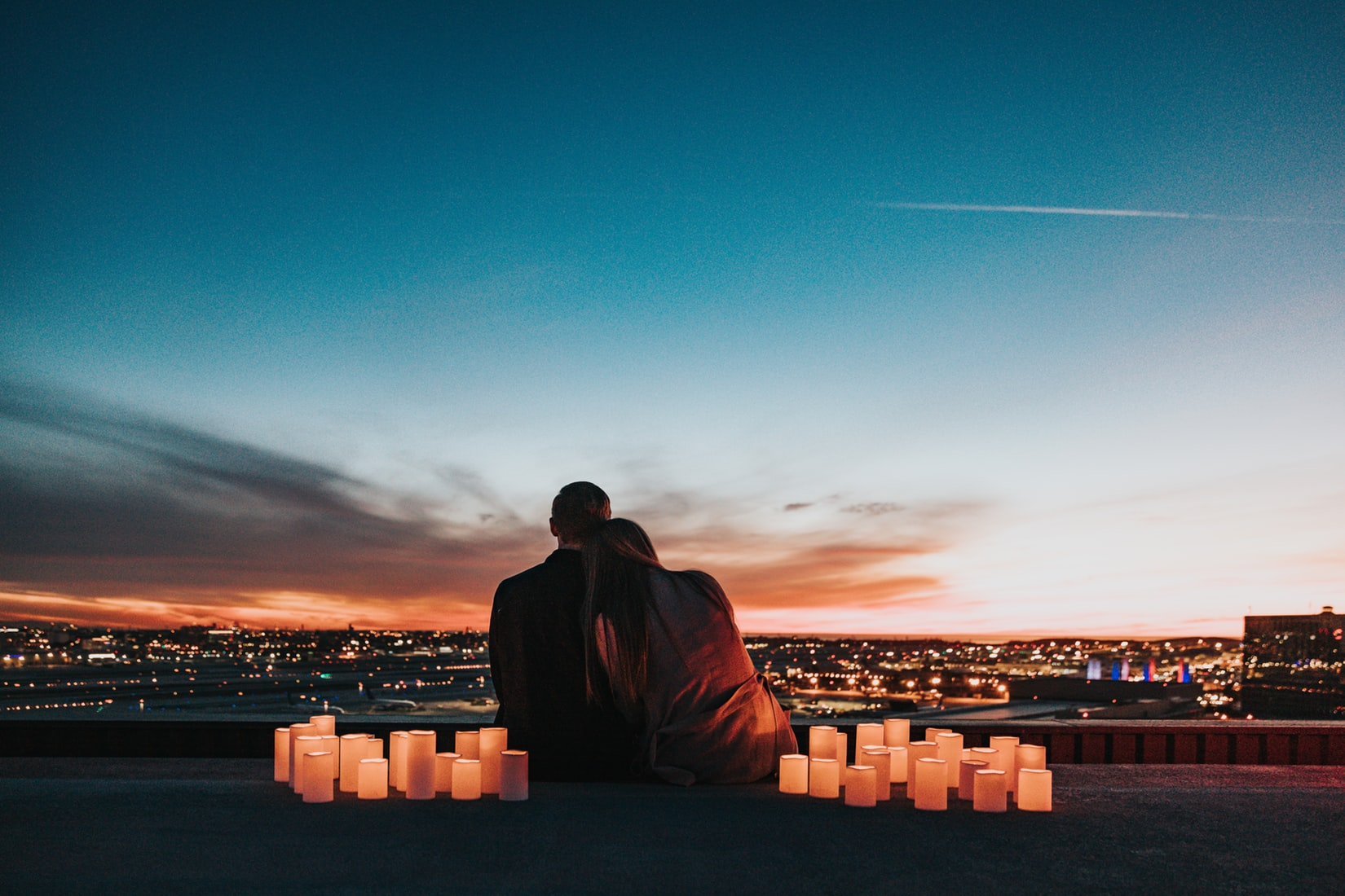 Couple in love sitting and facing the city at sunset