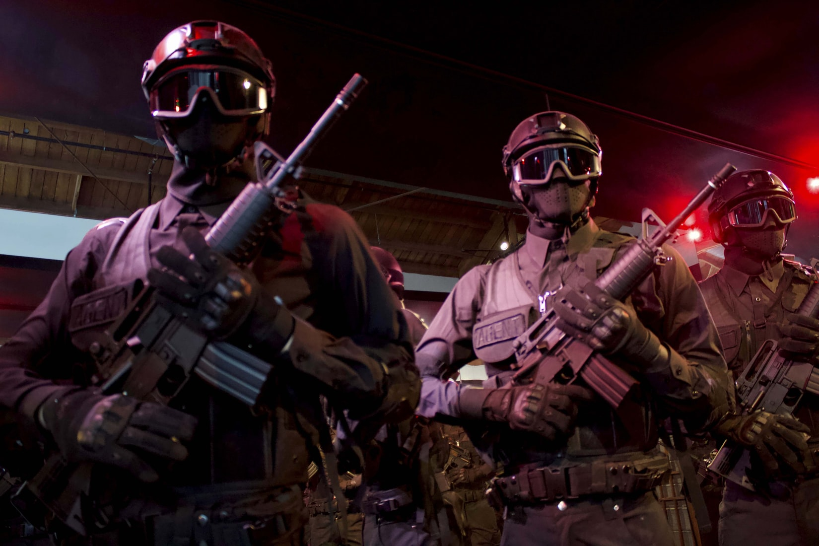 Officers with black goggles and assault rifles