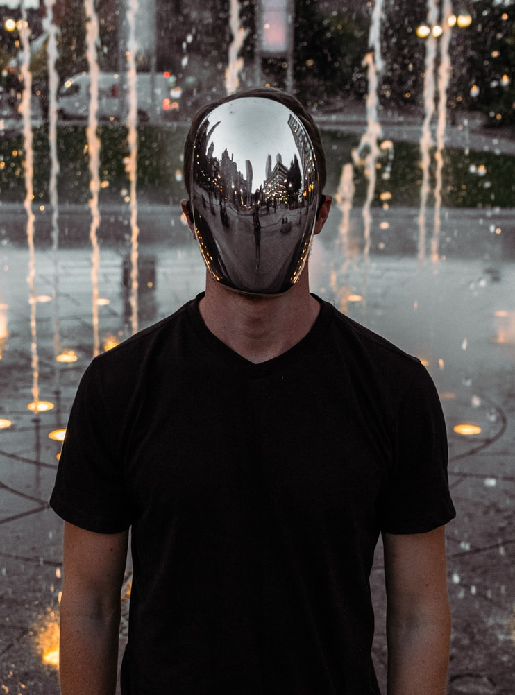 White man standing with silver reflective mask on face in front of yellow lights outside
