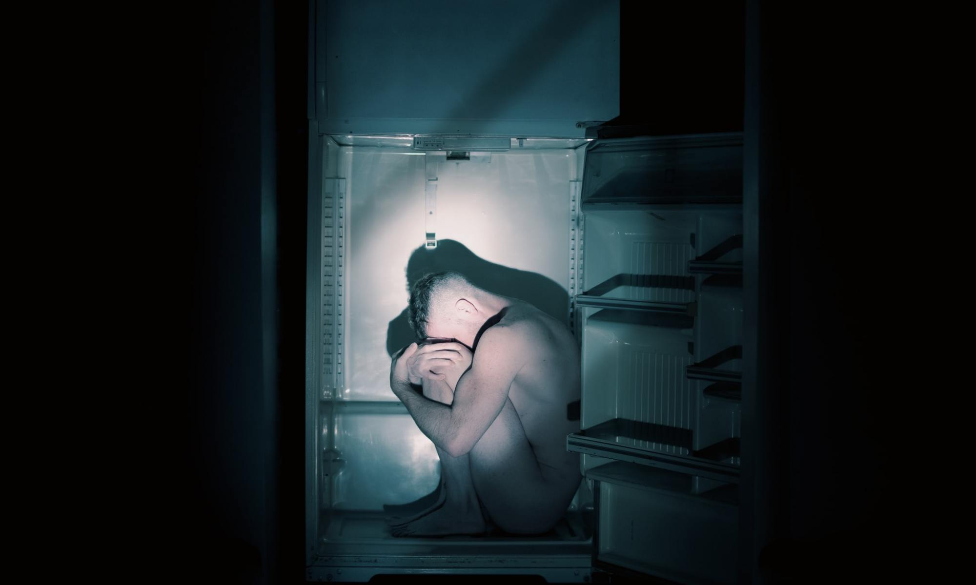 Naked man in dark room sitting in white refrigerator