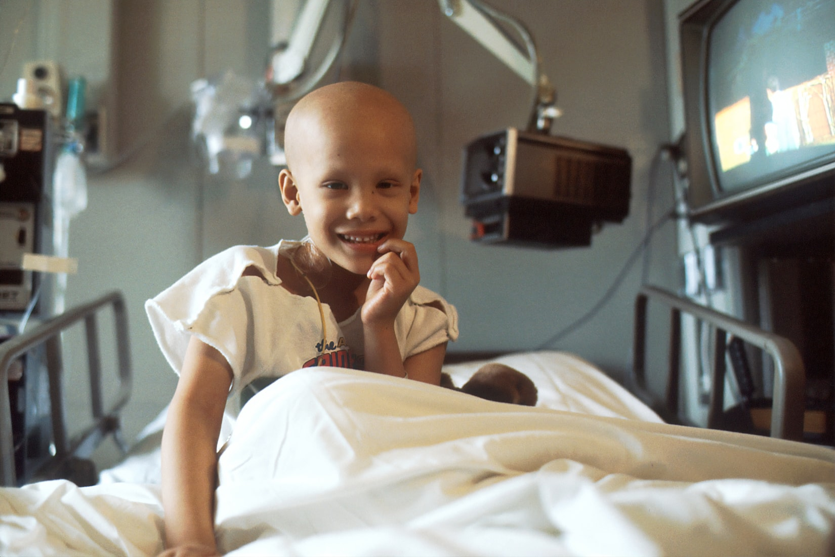 Child with cancer smiling while sitting on hospital bed