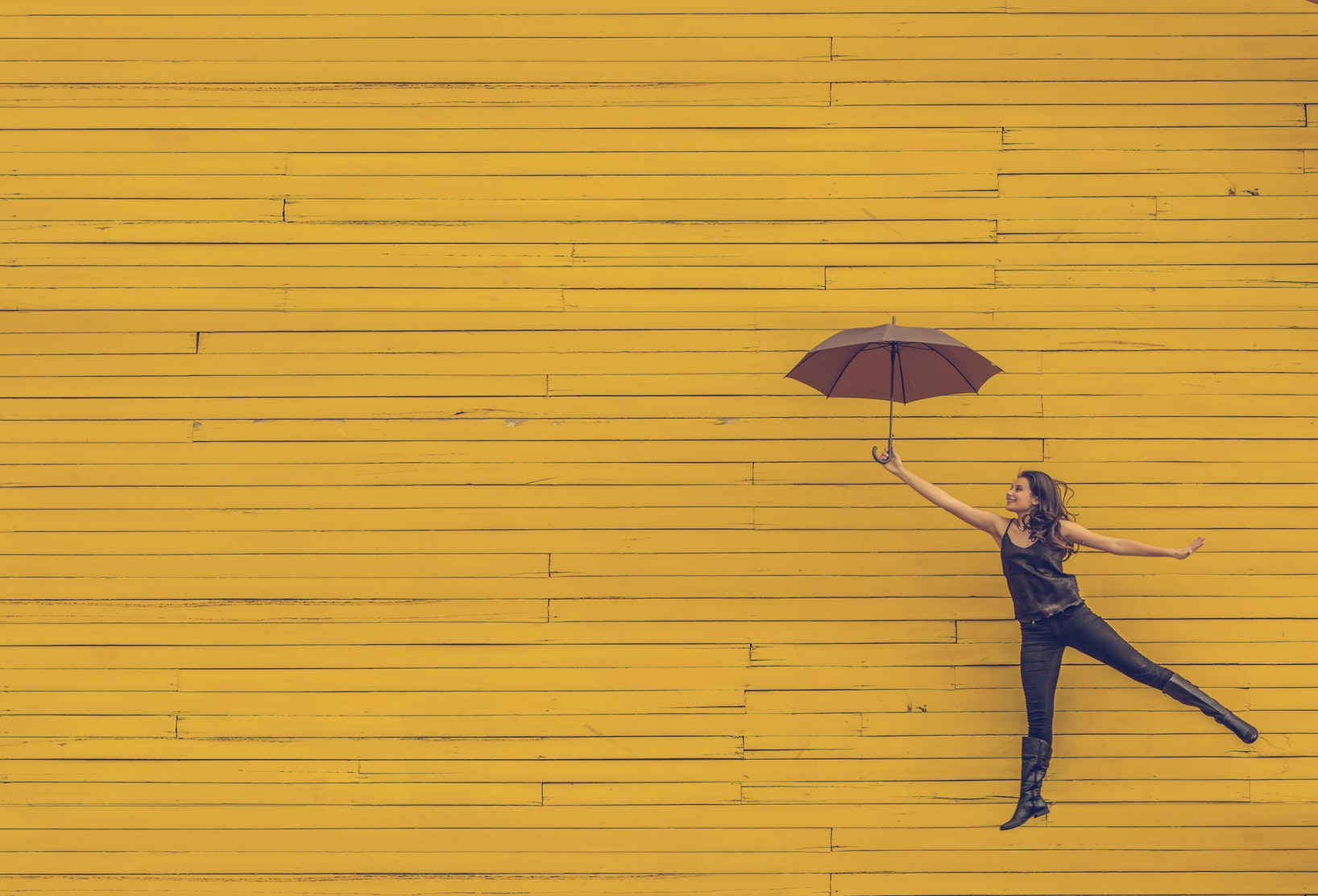 Brunette woman holding brown umbrella against yellow wall