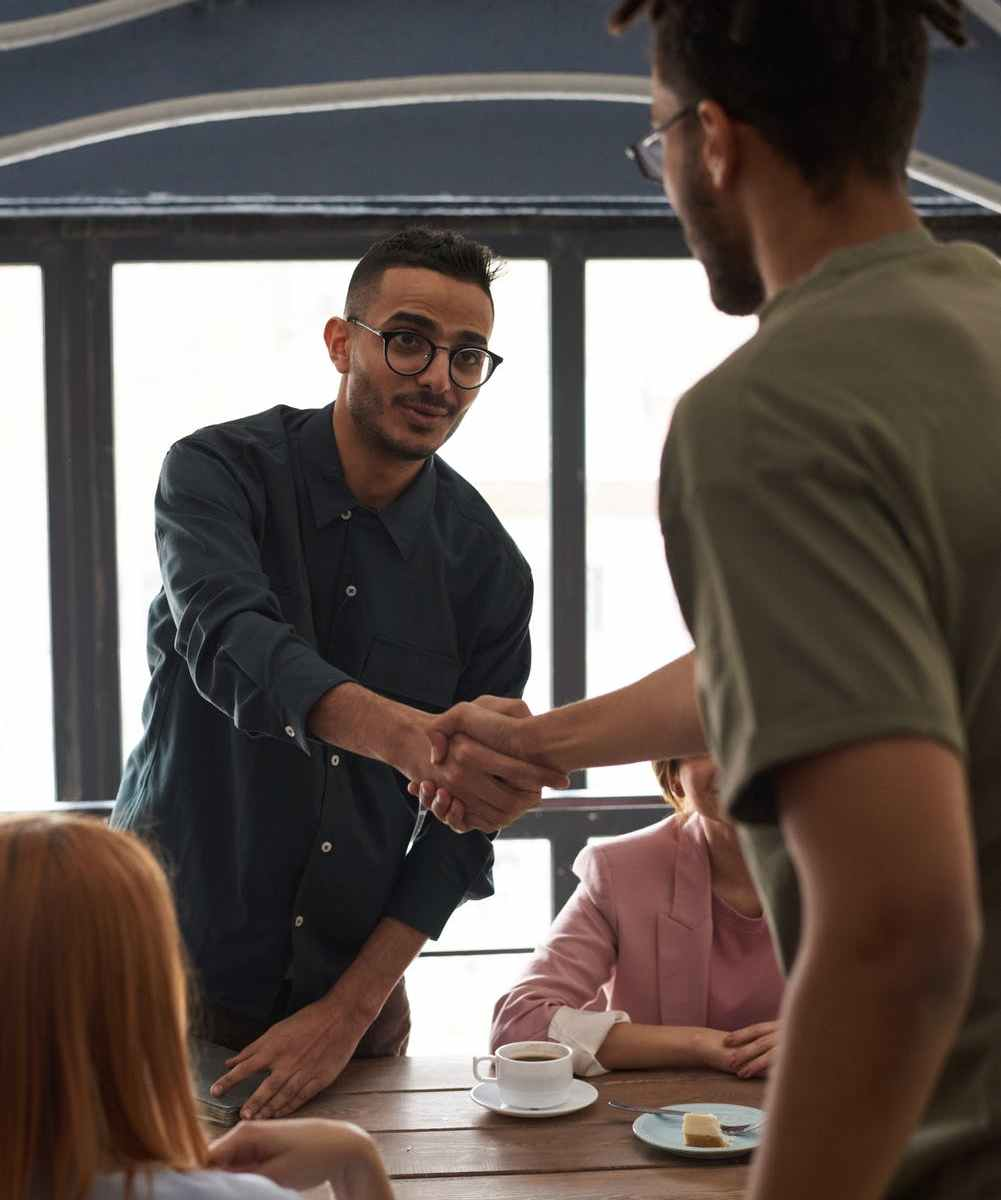 Young black man shaking hands with brown man across wooden table