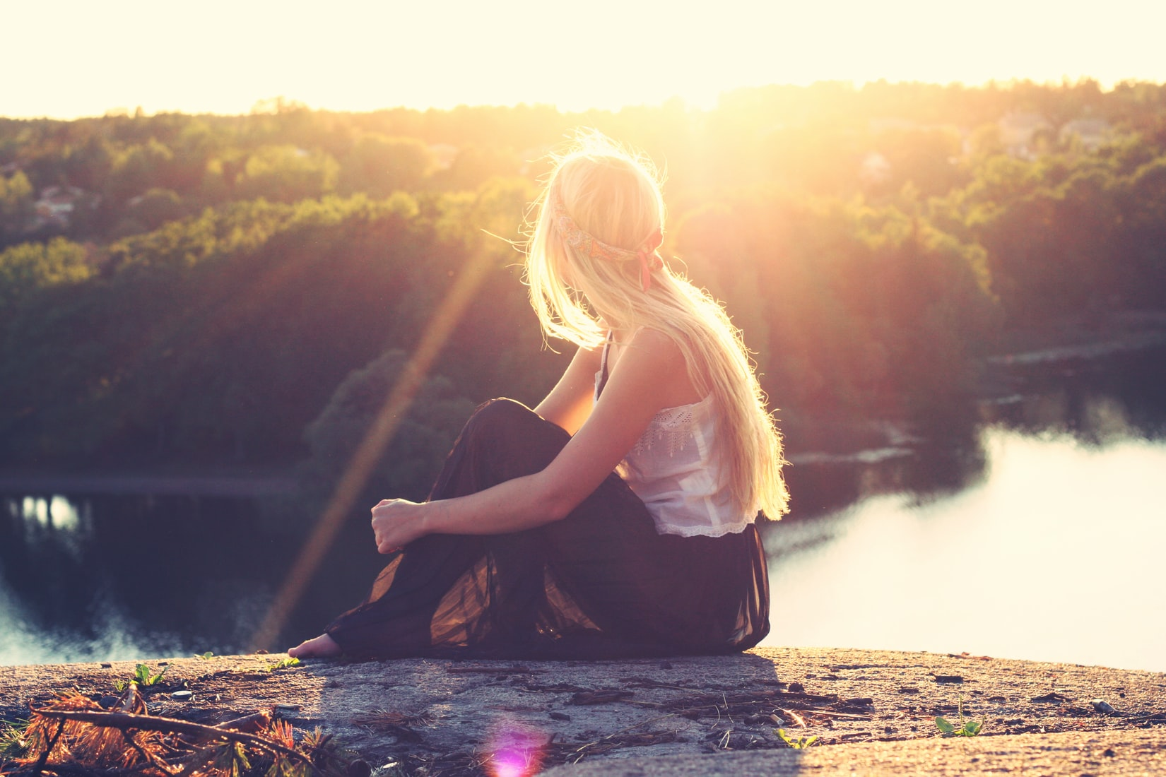 Young blonde woman sitting on cliff watching body of water and trees