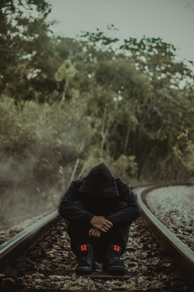 Depressed man wearing black hoodie with head down sitting on train track