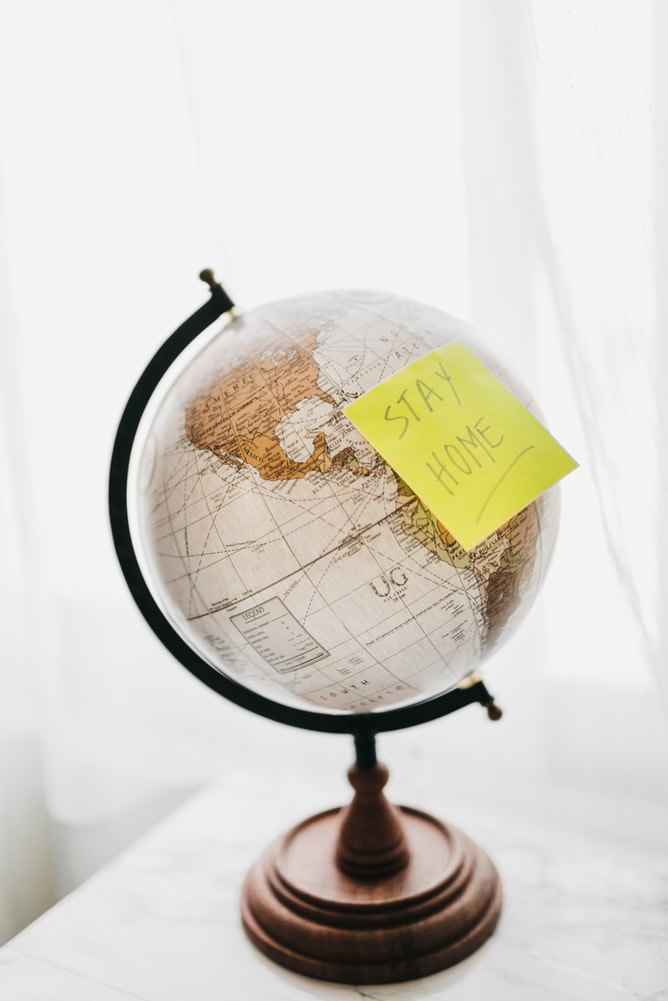 "Brown and black desk globe with yellow ""stay home"" sticky note on top of it"