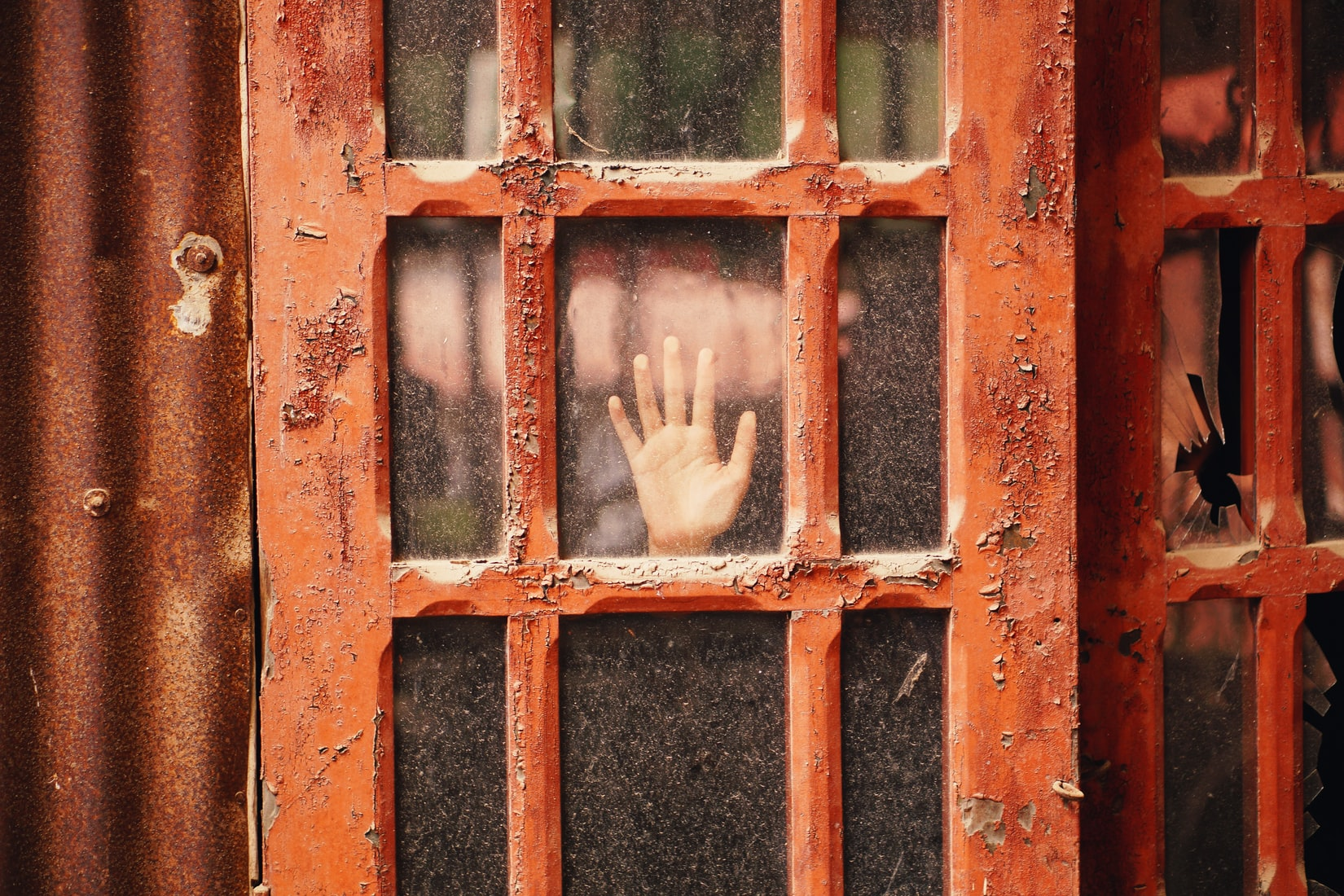 Scared person's hand on glass panel door with red wooden frame