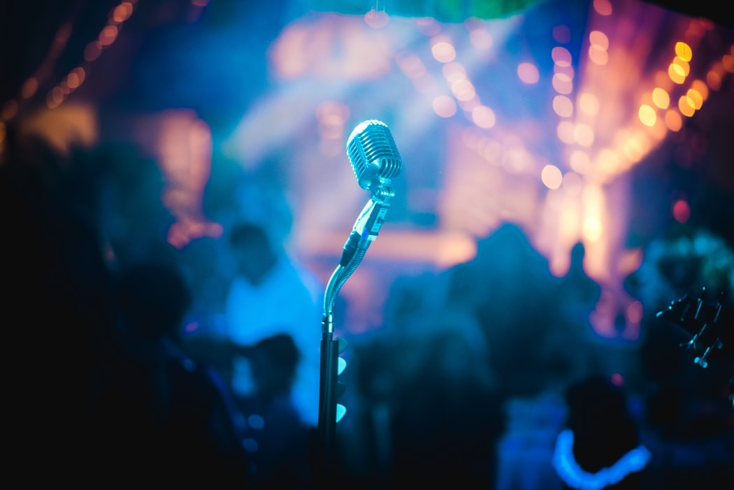 Gray microphone inside party room with bright orange lights and people in background