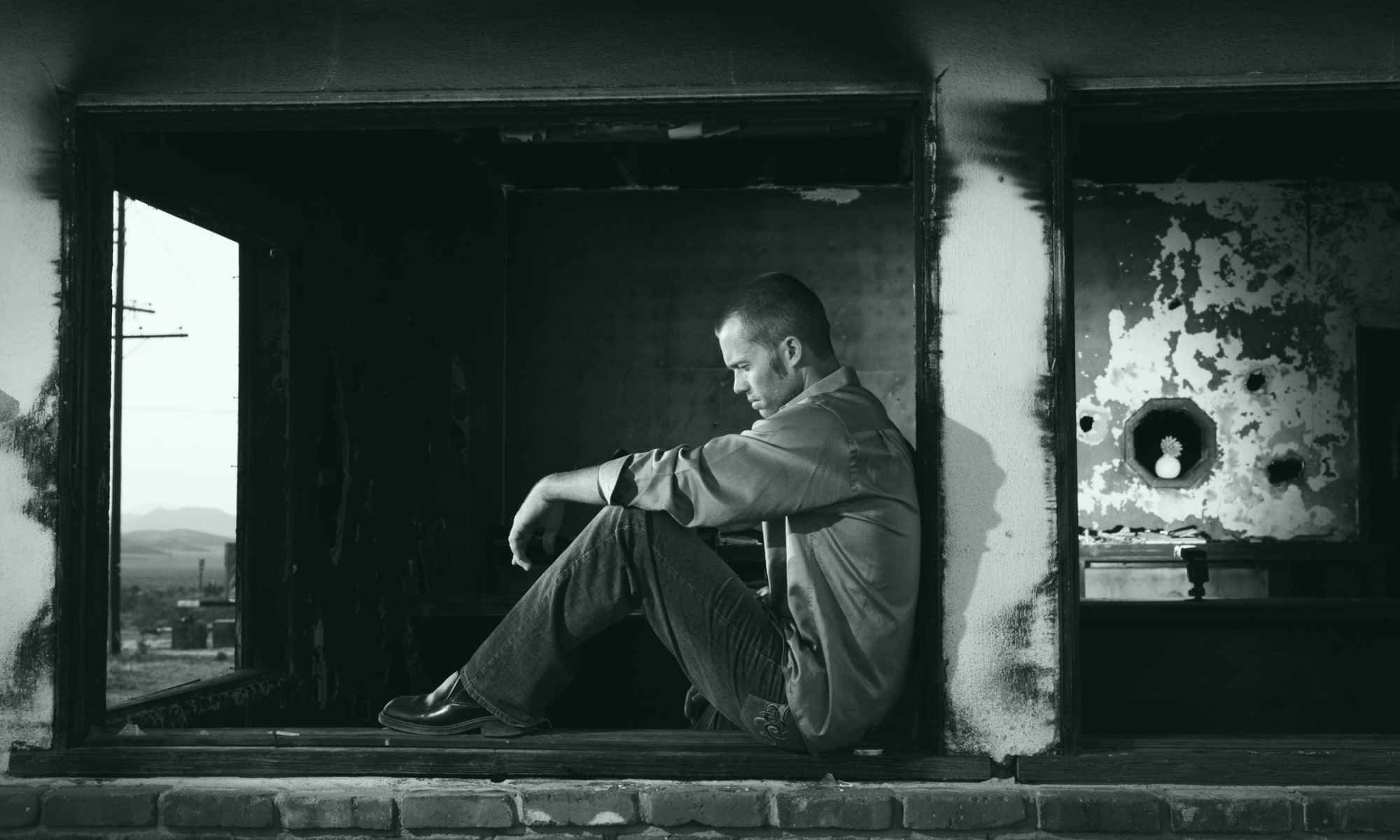 Grayscale photography of depressed man sitting against wall staring at ground