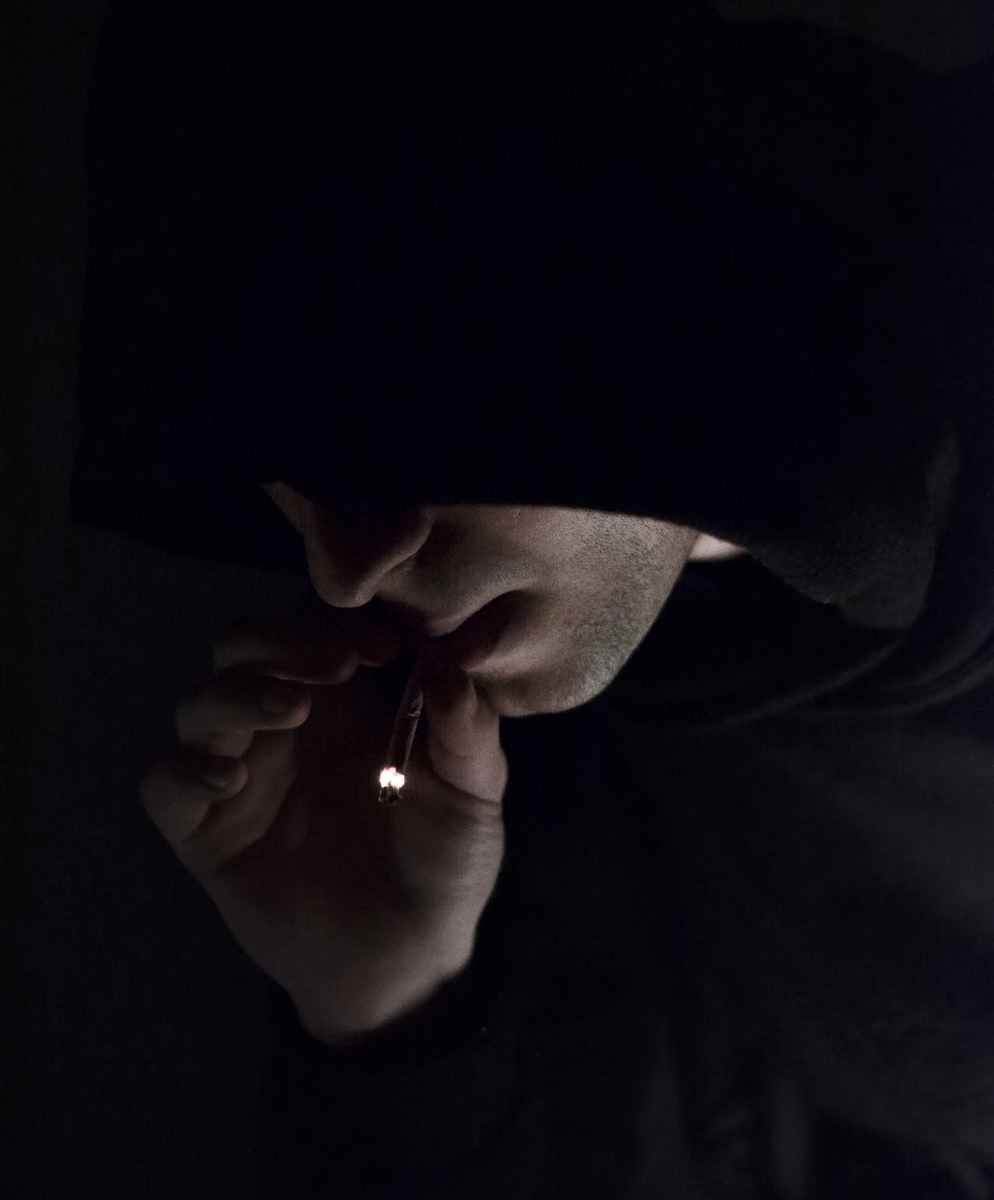 Teenage boy wearing black hoodie smoking marijuana joint