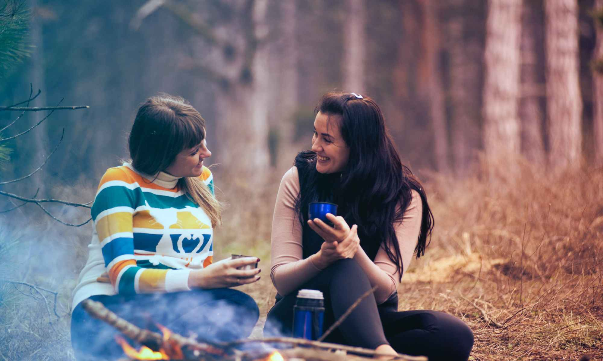 Two women smiling sitting in front of bonfire near forest