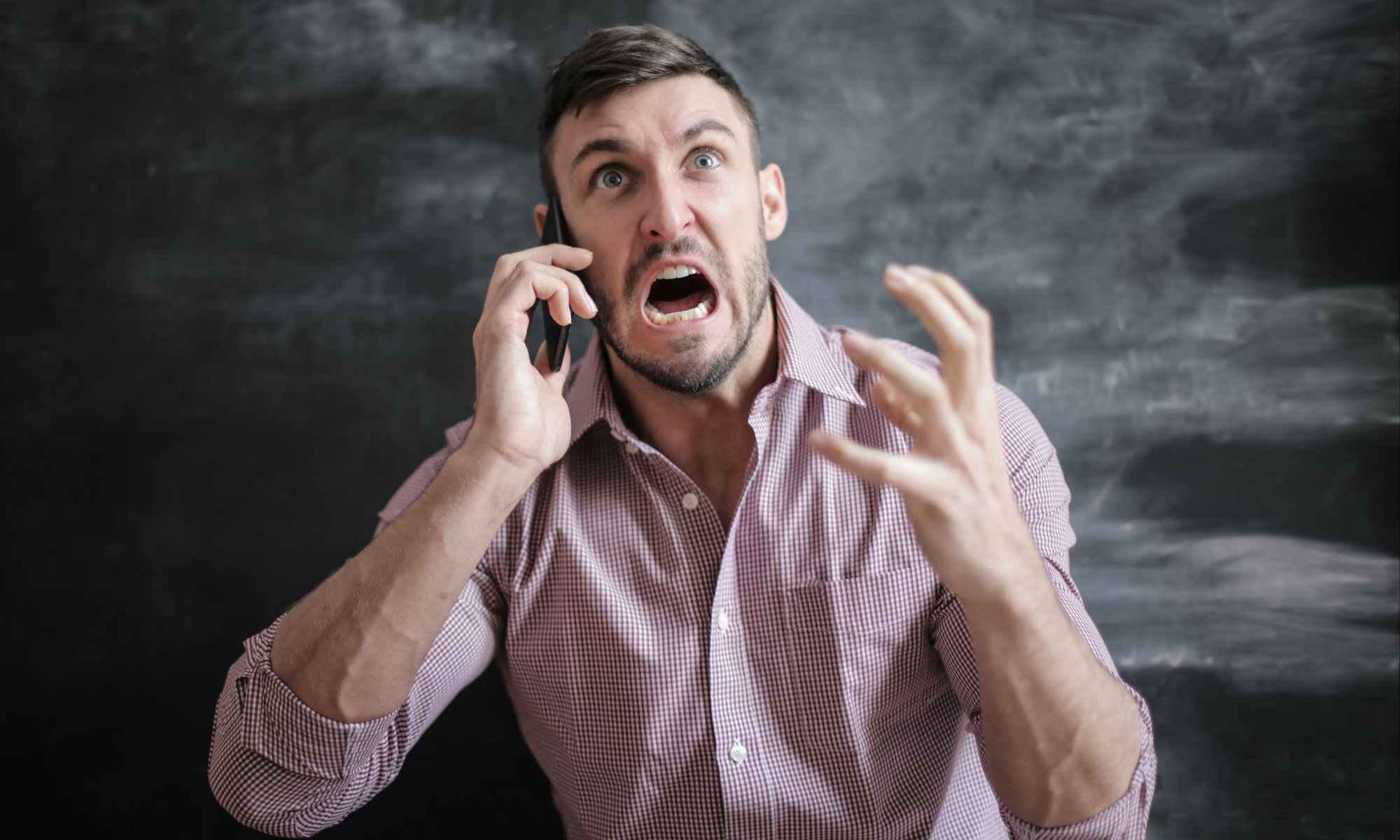 Manic and angry man yelling on cellphone