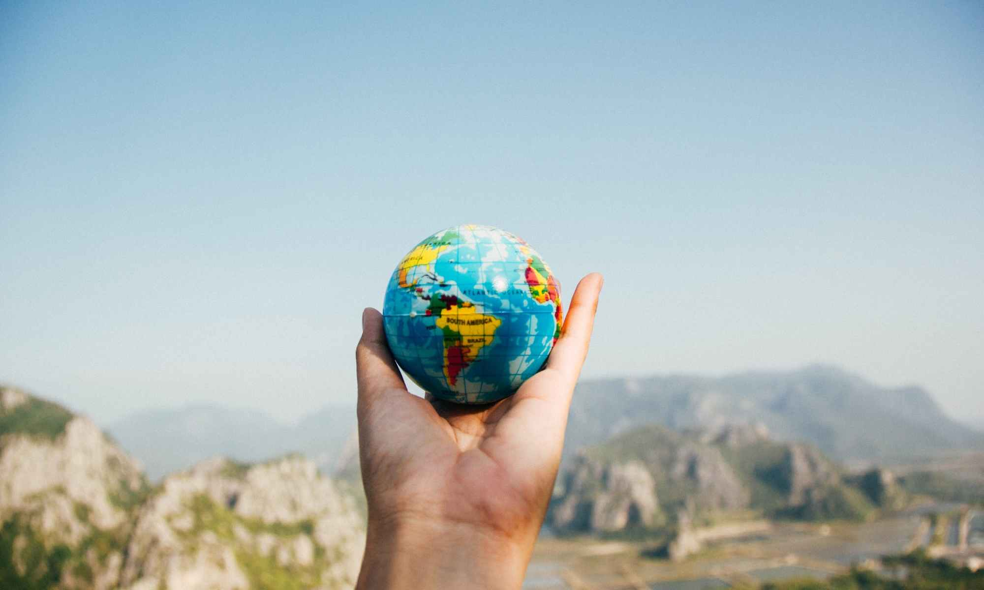 Hand holding mini globe in front of mountains