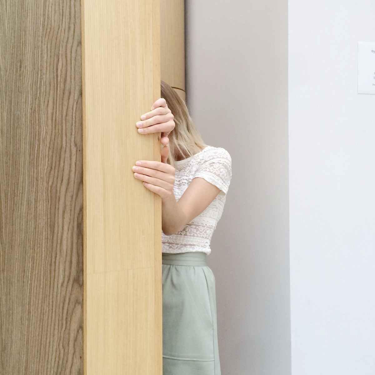 Scared blonde girl hiding behind wooden door
