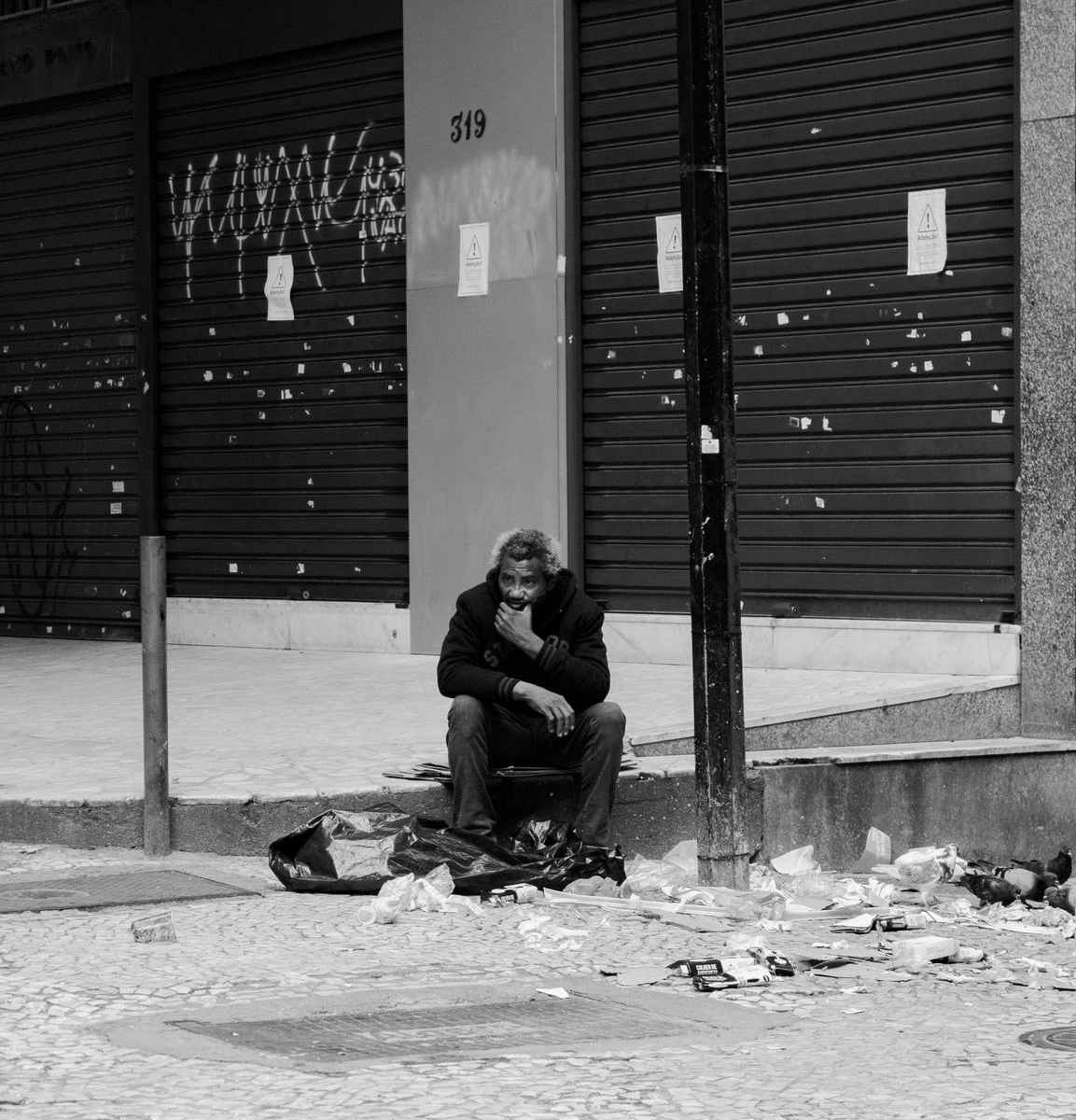 Psychotic black man sitting on sidewalk next to garbage on ground