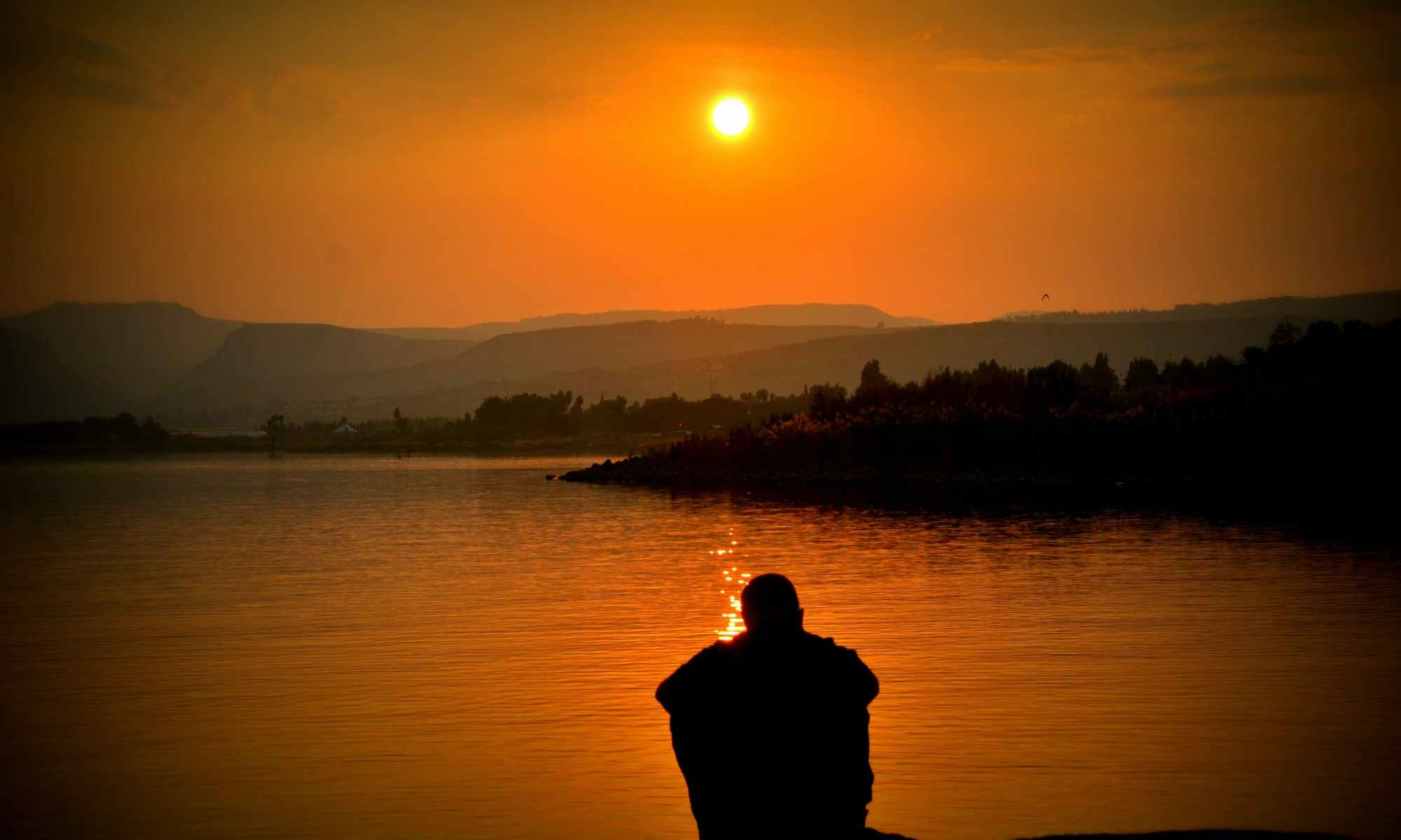 Man sitting by lake during sunset