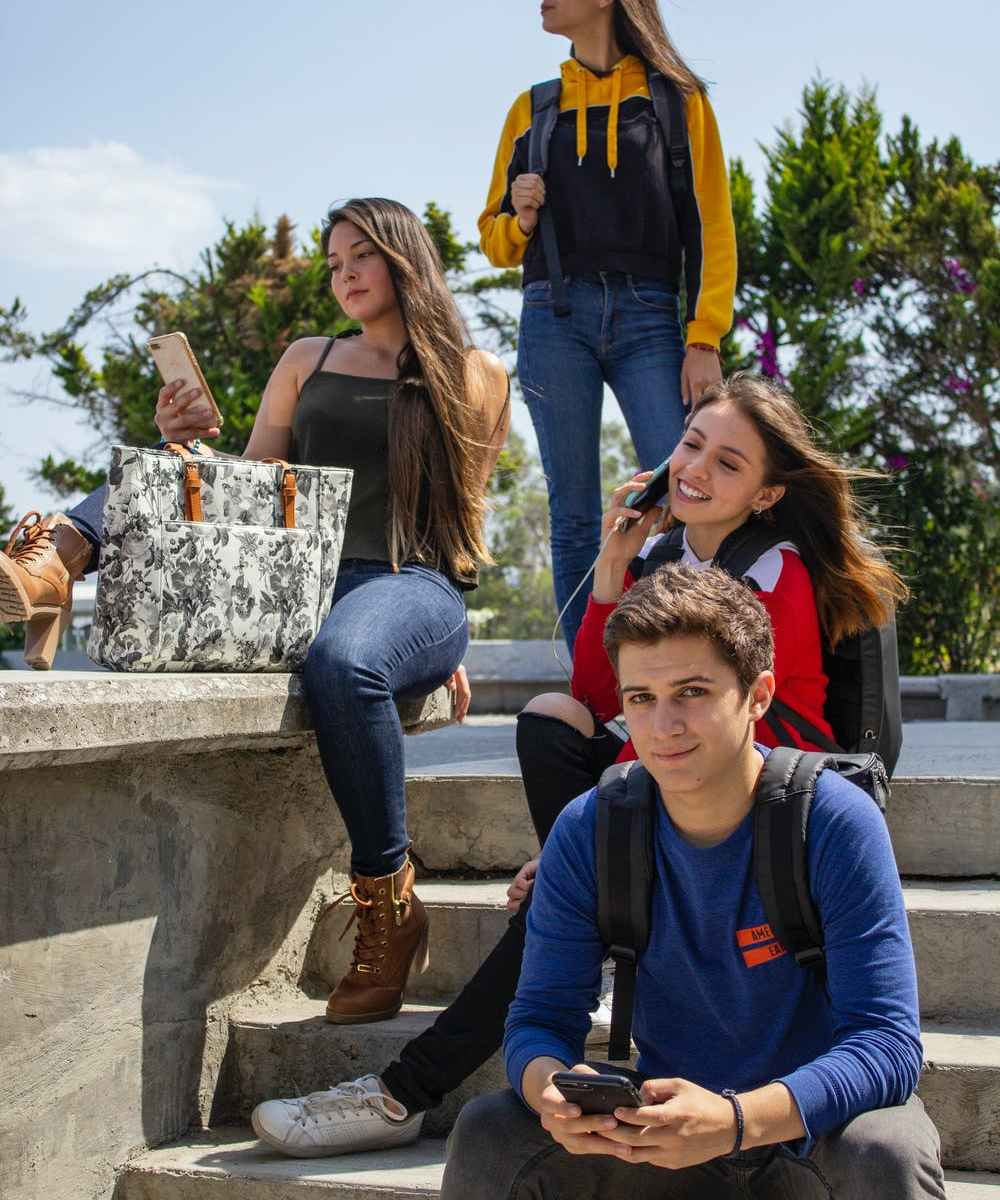Three girls and one boy sitting on steps outside holding cell phones
