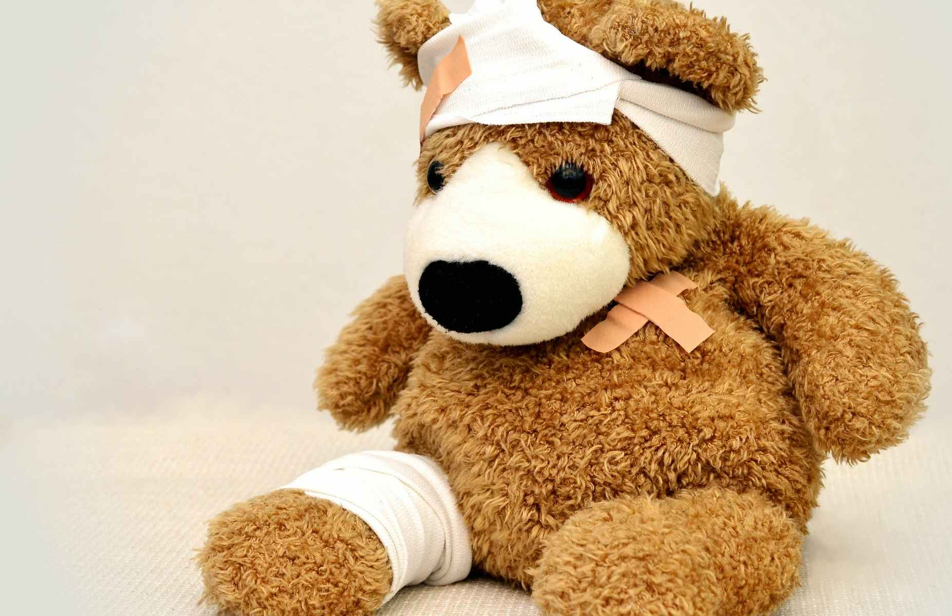 Brown teddy bear with bandaids over heart and white head scarf