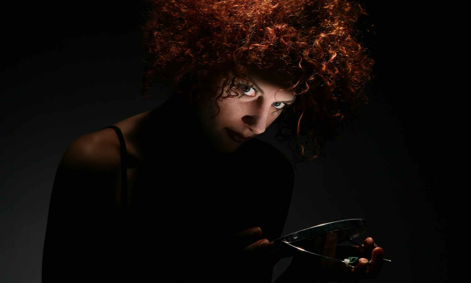 Schizophrenic woman with curly red hair holding small round mirror