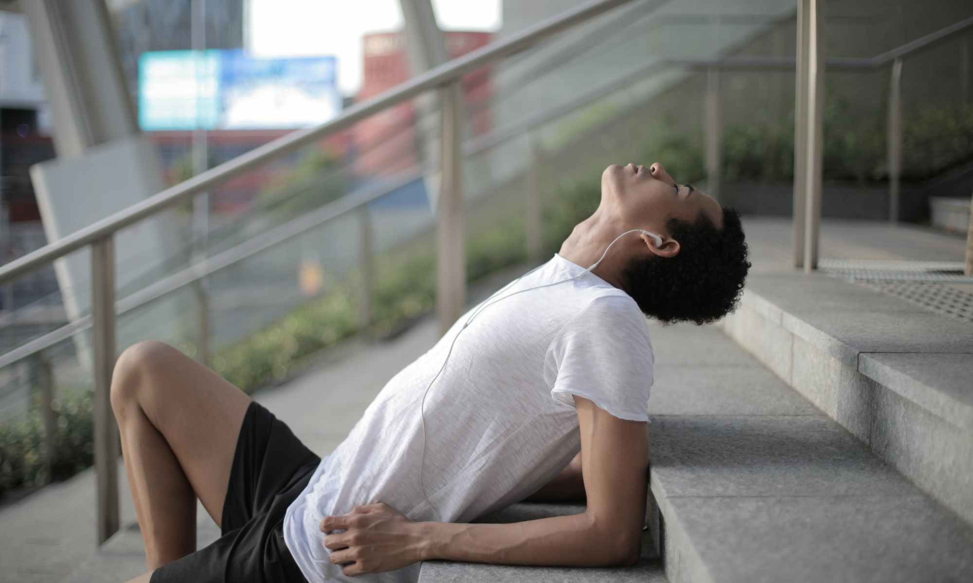 Asian man laying on steps outside with eyes closed listening to music