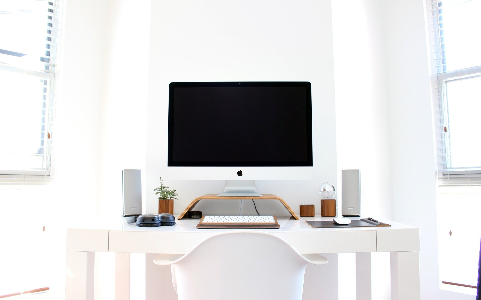 iMac computer on white desk in bright lit room