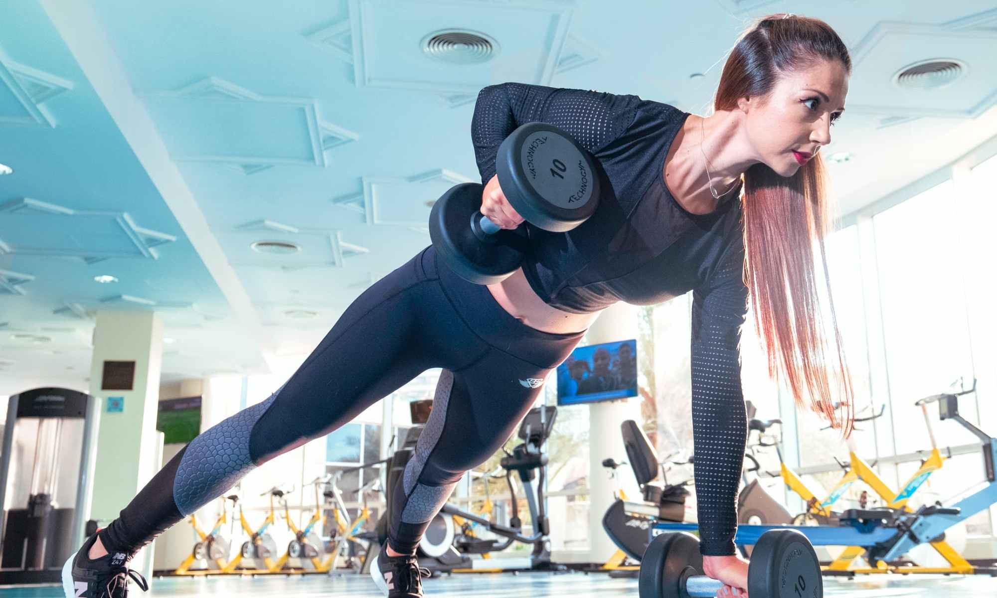 White woman dressed in black outfit working out with weights in gym