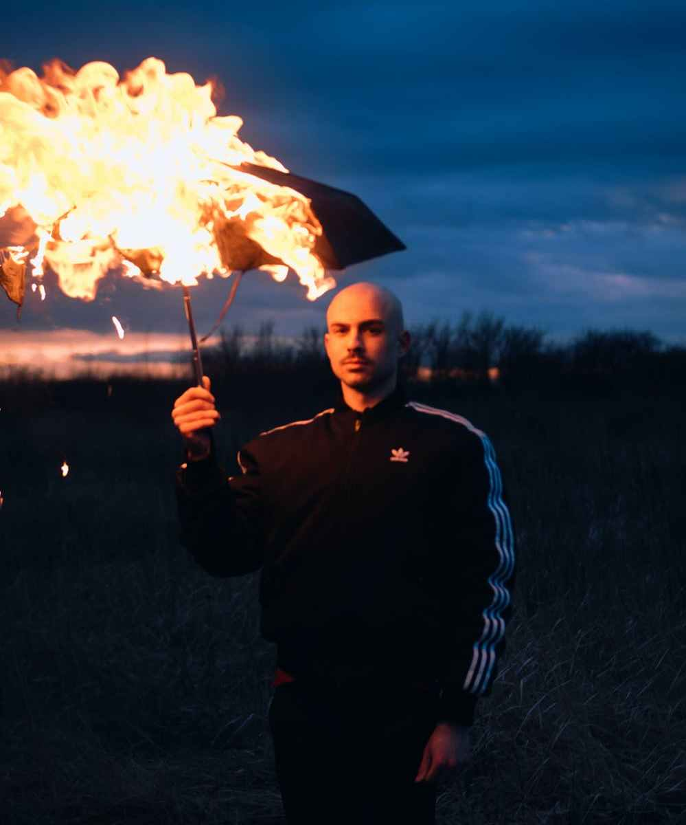Bald man in Adidas jumpsuit holding burning umbrella