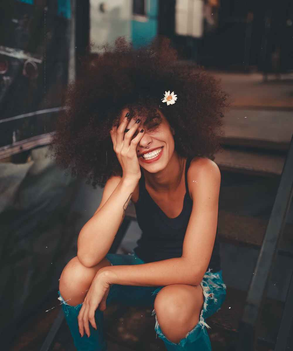 Photo of smiling ebony woman with afro sitting on stairs